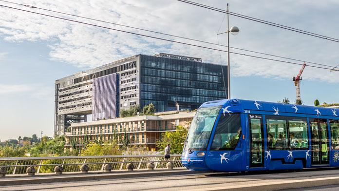 un tramway bleu passe devant la nouvelle mairie de Montpellier